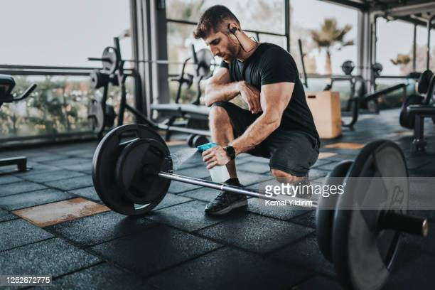 personal trainer disinfects sports equipment during new-normal - gym stock pictures, royalty-free photos & images