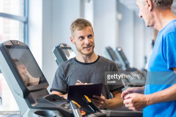 personal trainer explaining senior man exercise plan at rehab - drug rehab stock pictures, royalty-free photos & images