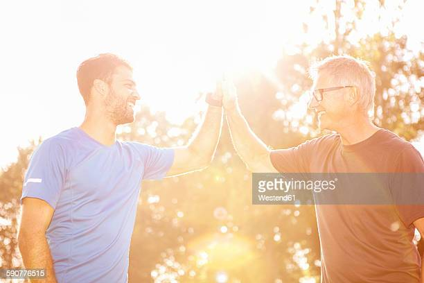Personal trainer giving client high five after training in a park