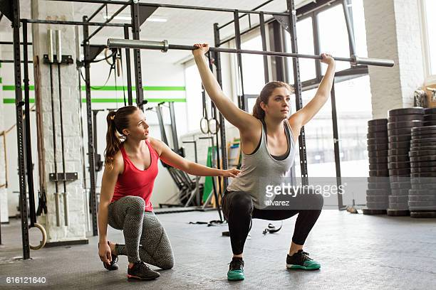 personal trainer guiding woman doing barbell squats at gym - training course stockfoto's en -beelden