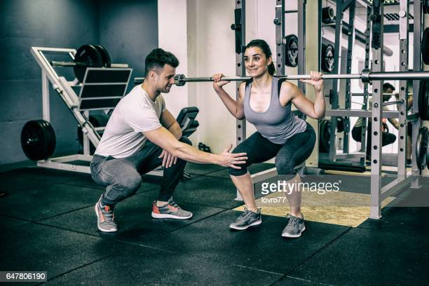 Personal trainer help sportswoman workout with dumbbells at the gym