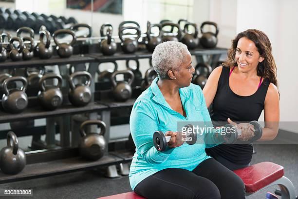 Entraîneur personnel aidant afro-américain senior dans la salle de sport