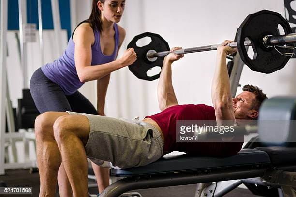 d0c86874296 Personal Trainer Assisting A Client In The Gym Stock Photos and ...