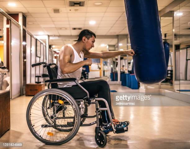 personal trainer helping patient in wheelchair in the gym - sports medicine stock pictures, royalty-free photos & images