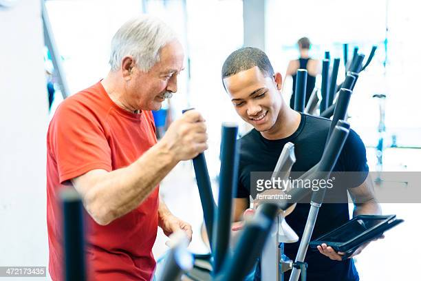 Personal Trainer Helping Senior man in GYM