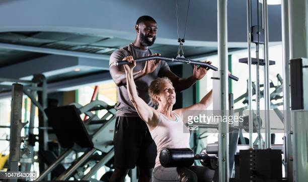 personal trainer helping senior woman at gym - strength training stock pictures, royalty-free photos & images