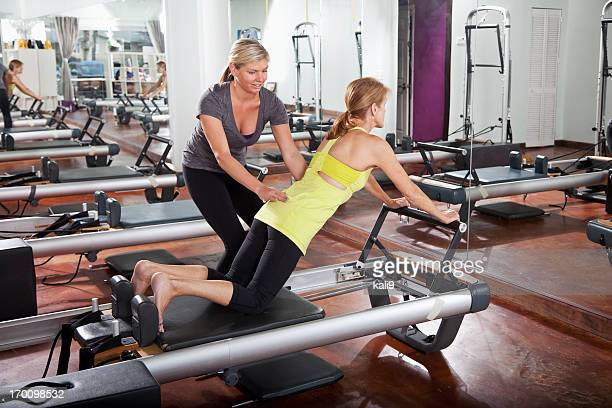 Personal trainer helping woman on pilates reformer