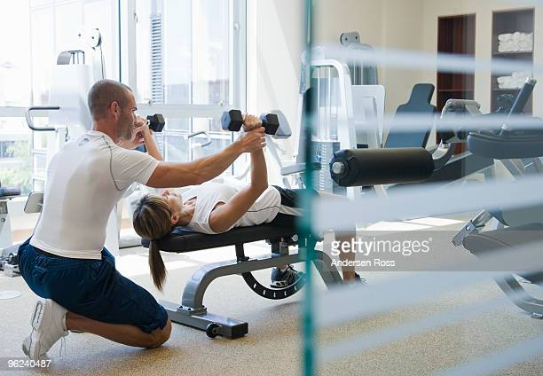 personal trainer helping woman work out - fitness instructor stock pictures, royalty-free photos & images