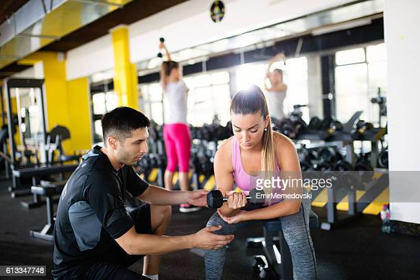 Personal trainer helping young sporty woman workout with dumbbells