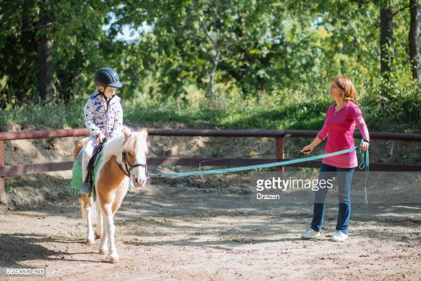 personal trainer in horseback riding school for kids teaching trot - recreational horseback riding stock pictures, royalty-free photos & images