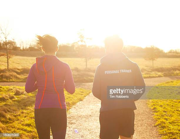 Personal trainer jogging with runner.