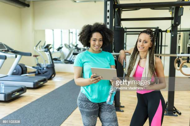 personal trainer looking at test results on digital tablet - center athlete stock photos and pictures