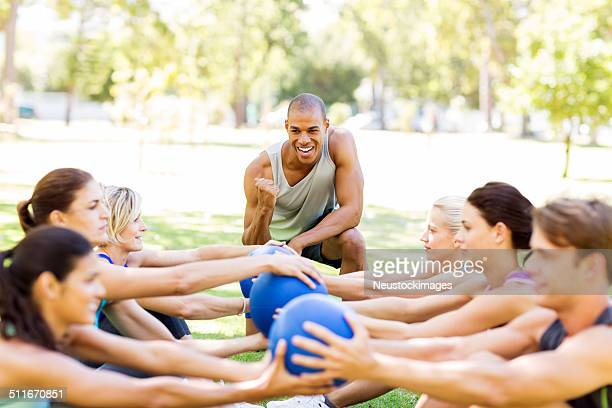 personal trainer motivating people exercising with medicine ball - barracks stock pictures, royalty-free photos & images