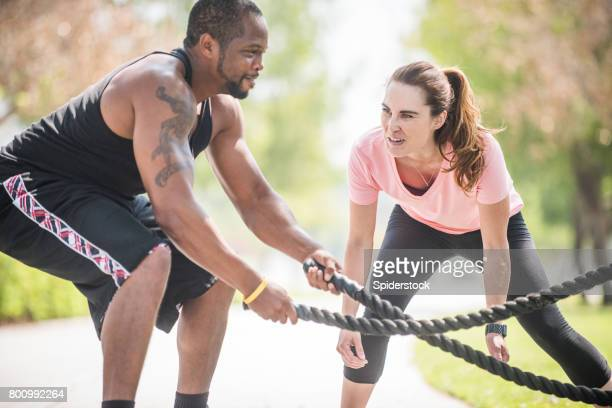 Personal Trainer Supporting Client Doing gym Ropes