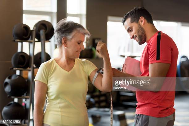 Personal trainer taking measurements of a senior woman at the gym