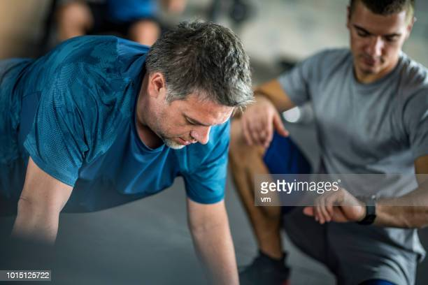personal trainer timing his client in a plank position - fitness instructor stock pictures, royalty-free photos & images