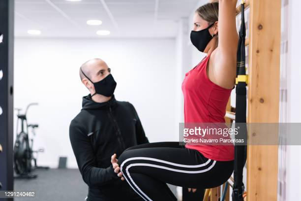 personal trainer wearing a mask helping a woman work out on a wooden staircase at a gym - turner syndrome stock-fotos und bilder