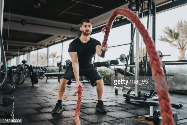 personal trainer working with battle rope after quarantine - gym stock pictures, royalty-free photos & images