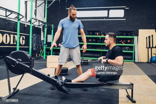 Personal trainer working with man with disability in gym