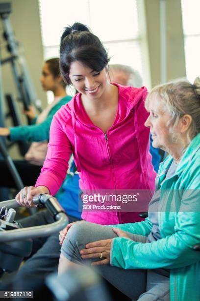 Persönlicher Trainer arbeitet mit leitender Client auf Übung Maschine