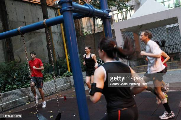 Personal trainner Geoff Hindmarsh leads some bankers doing intense early morning circuit training in Central 24FEB12