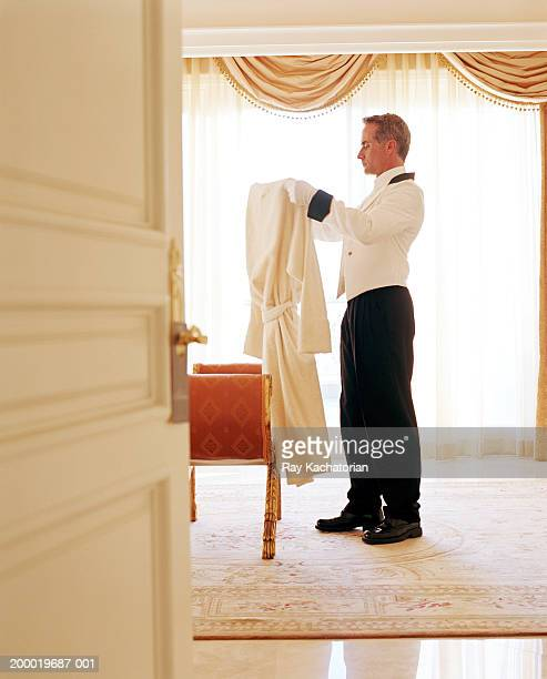 personal valet holding bathrobe - butler stock pictures, royalty-free photos & images
