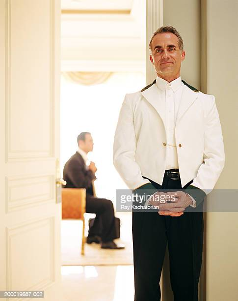 Personal valet standing outside room, businessman in background