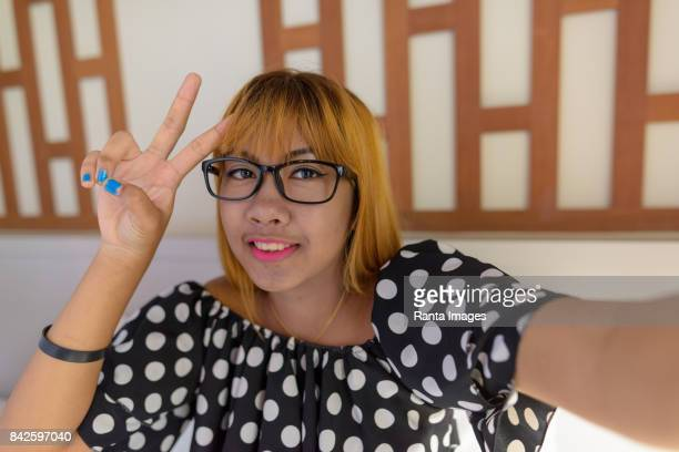 Personal view of young Asian teenage girl vlogging in the bedroom at home