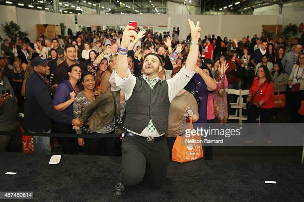 Personality Adam Richman takes a selfie with guests after his presentation on KitchenAid stage at the Grand Tasting presented by ShopRite featuring...