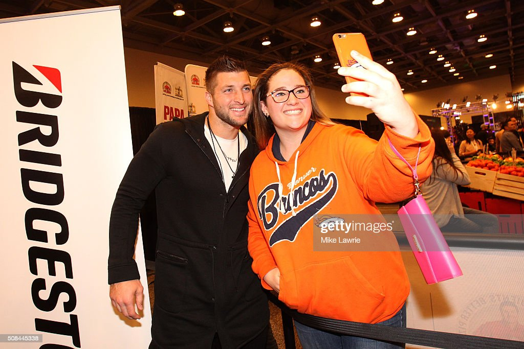 TV personality and former NFL player Tim Tebow poses with a fan on Radio Row in the Moscone Center West prior to Super Bowl 50 on February 4, 2016 in San Francisco, United States.