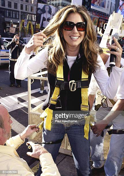 TV personality Daisy Fuentes has a safety harness put on before being hoisted in a cherry picker to place the last pink PostIt note on the world's...