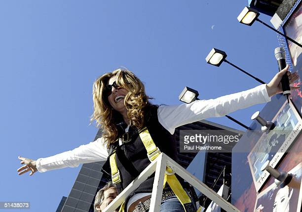 TV personality Daisy Fuentes is hoisted on a cherry picker to place the last pink PostIt note on the world's largest pink ribbon made of PostIt notes...