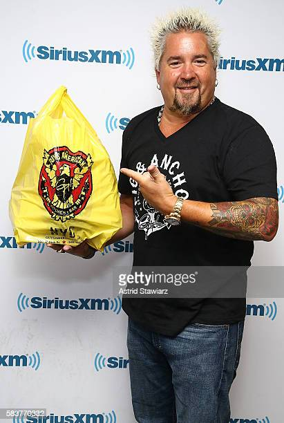 TV personality Guy Fieri holds a bag of food from his restaurant Guy's American Kitchen Bar at the SiriusXM Studios on July 27 2016 in New York City