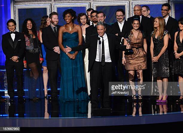Personality John Stewart and cast of crew of The Daily Show accept their award onstage during the 64th Primetime Emmy Awards at Nokia Theatre LA Live...