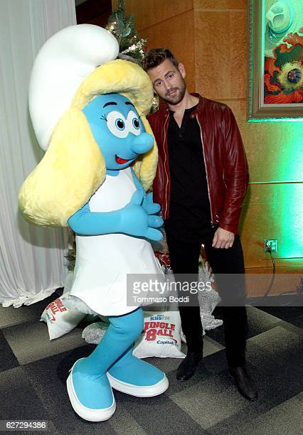 TV personality Nick Viall poses with Smurfette at the 1027 KIIS FM Artist Gift Lounge presented by FUJIFILM INSTAX at iHeartRadio's Jingle Ball 2016...