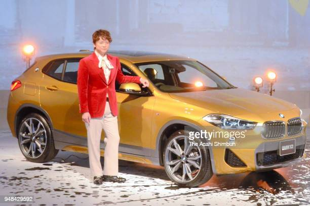 TV personality Shingo Katori stands next to the BMW's new sport utility vehicle 'X2' during its unveiling on April 16 2000 in Tokyo Japan