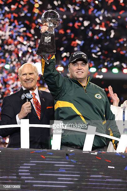 TV personality Terry Bradshaw looks on as head coach Mike McCarthy of the Green Bay Packers holds up the Vince Lombardi Trophy after winning Super...