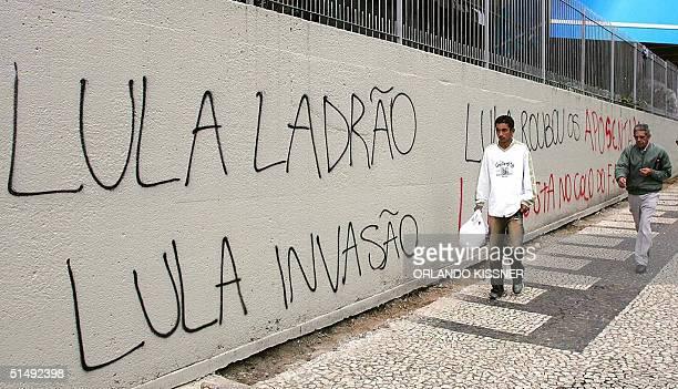 Personas pasan delante de un muro donde aparecen escritas leyendas contra el presidente Luiz Inacio Lula Da Silva, el 18 de octubre de 2004, en...
