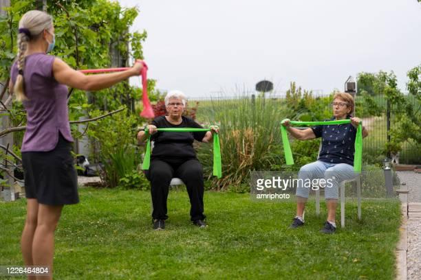personel fitness coach während der therapie mit seniorin im ruhestand gemeinschaftsgarten - turner syndrome stock-fotos und bilder