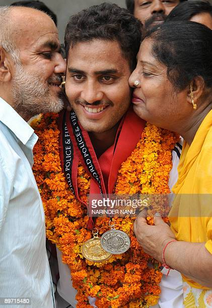 Personel from the Punjabi police Vikram Sharma is congratulated by his father Kamal Kishore Sharma and mother Kanchan Sharma on his return from the...