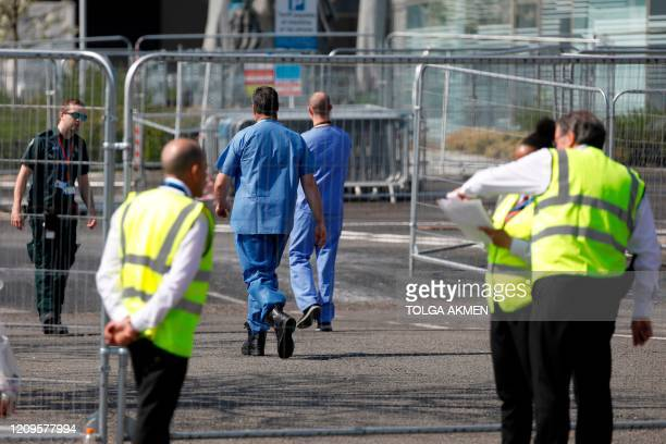 Personel walk outside the NHS Nightingale field hospital comprising of two wards each of 2000 people at the ExCel centre in London on April 10 to...