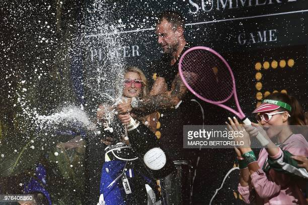 US personnality and model Paris Hilton and German fashion designer Philipp Plein spray champagne as they acknowledge the audience at the end of the...