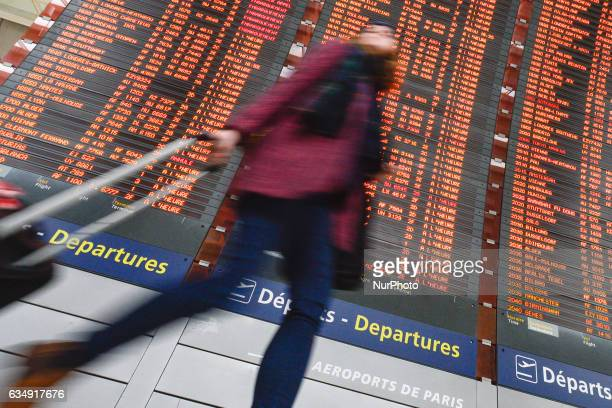 Personne passes in front of the Departures board at the Terminal 2 of Paris Charles de Gaulle Airport. On Sunday, 12 February in Paris, France.