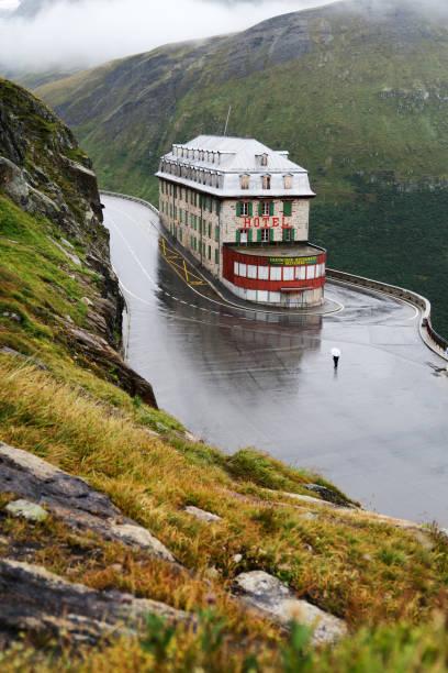 Personne seule sous la pluie face a l'hôtel belvédère abandonné, au sein du virage de furkapass (Suisse), le 29 aout 2020