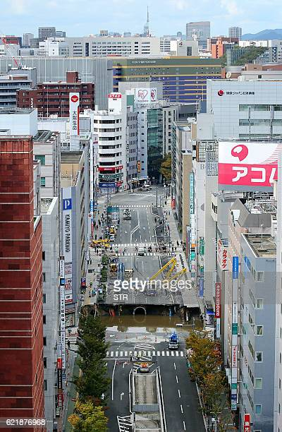 Personnel are seen by a giant sinkhole as they work to fill the hole that appeared in the middle of Fukuoka's bustling business district swallowing...
