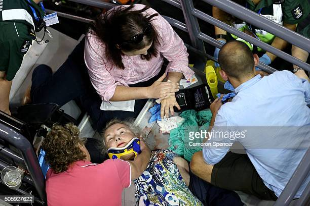 Personnel attend to a spectator during a break in play on Rod Laver Arena during the second round match between Ana Ivanovic of Serbia and Anastasija...