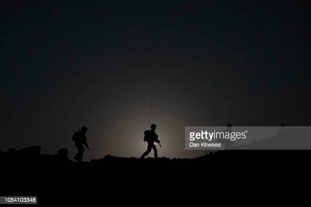 Personnel from 40 Commando, Royal Marines walk across a ridge with the moon setting behind during exercise 'Saif Sareea 3' on October 24, 2018 in...
