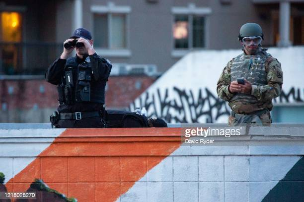 Personnel from the Seattle Police Department and the Washington National Guard keep an eye on demonstrators from a rooftop near the Seattle Police...