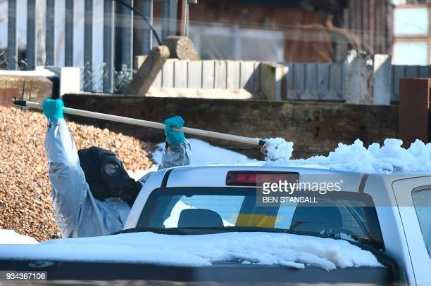 A personnel in protective coveralls with breathing equipment clears snow from the roof of a vehicle on the grounds of a cement plant in the village...