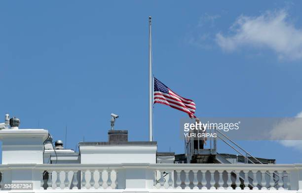 Personnel leave after lowering the US flag to halfstaff at the the White House in Washington DC following US President Barack Obama's statement on...